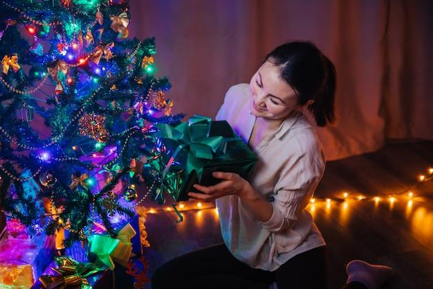 Una joven asiática con una sonrisa en su rostro sostiene una caja de regalo de navidad verde en sus manos. fondo de navidad con árbol de navidad, guirnaldas y regalos.