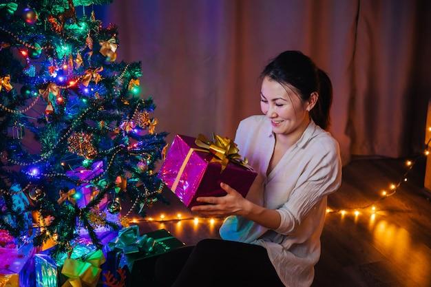 Una joven asiática con una sonrisa en su rostro tiene en sus manos una caja de regalo de navidad de color morado con un lazo amarillo. fondo de navidad con árbol de navidad, guirnaldas y regalos.