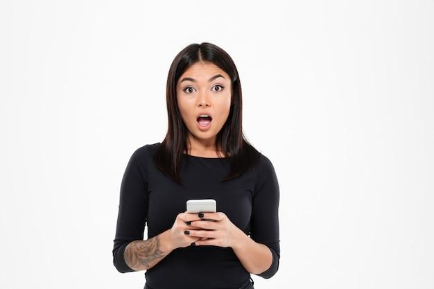 Joven asiática sorprendida chateando por teléfono móvil