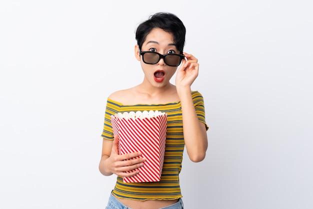 Joven asiática sorprendida con gafas 3d y sosteniendo un gran cubo de palomitas de maíz