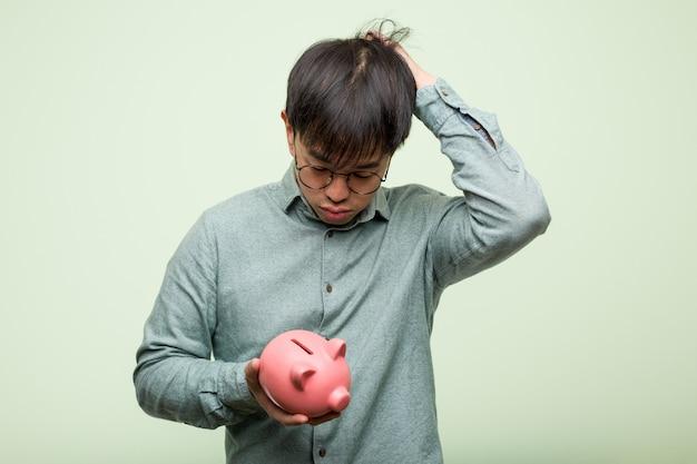 Joven asiática sosteniendo una alcancía preocupado y abrumado
