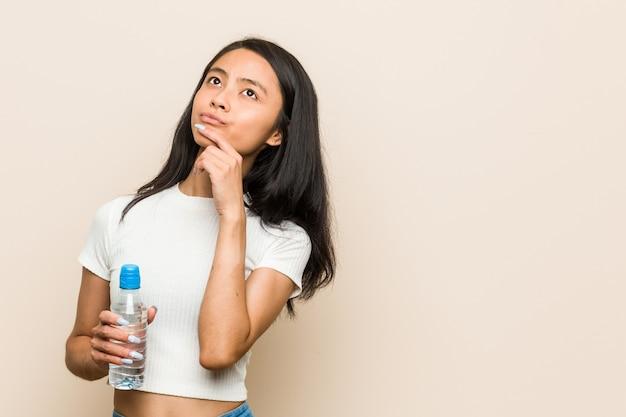 Joven asiática sosteniendo una botella de agua mirando hacia los lados con expresión dudosa y escéptica.