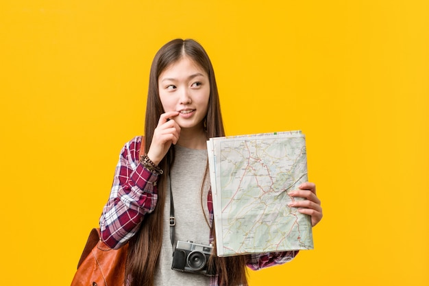 Joven asiática sosteniendo un mapa relajado pensando en algo