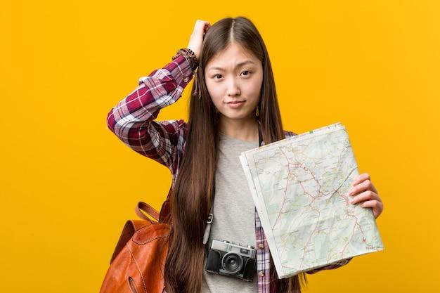 Joven asiática sosteniendo un mapa sorprendido, ha recordado una reunión importante