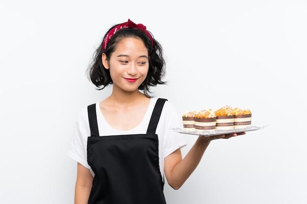 Joven asiática sosteniendo un montón de pastel de muffin sobre pared blanca aislada con expresión feliz