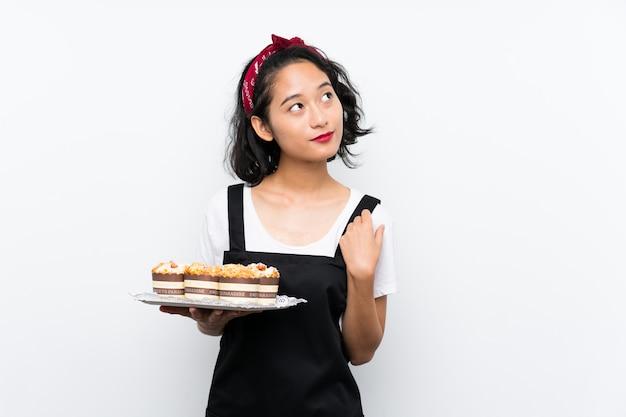 Joven asiática sosteniendo un montón de pastel de muffins sobre la pared blanca mirando hacia arriba mientras sonríe