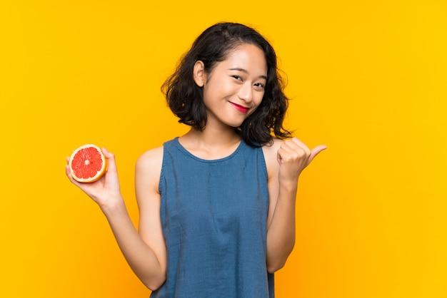 Joven asiática sosteniendo una toronja sobre pared naranja aislada apuntando hacia el lado para presentar un producto