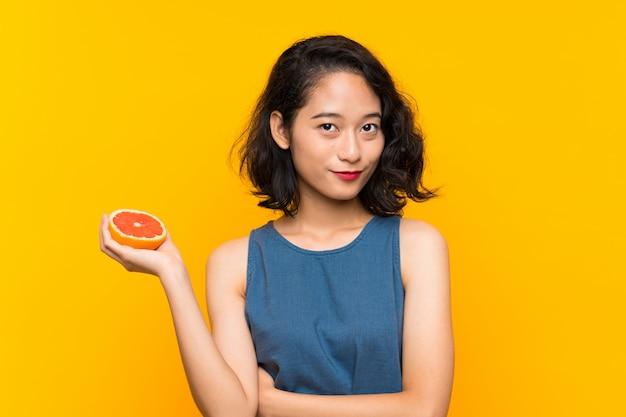 Joven asiática sosteniendo una toronja sobre pared naranja aislada mirando hacia arriba mientras sonríe