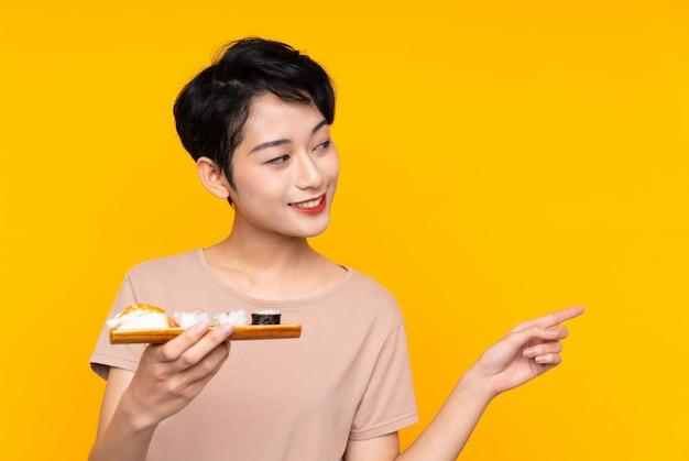 Joven asiática con sushi apuntando a un lado para presentar un producto
