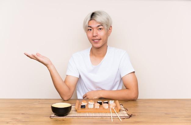 Joven asiática con sushi en una mesa con copyspace imaginario en la palma