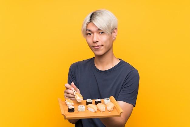 Joven asiática con sushi sobre amarillo aislado