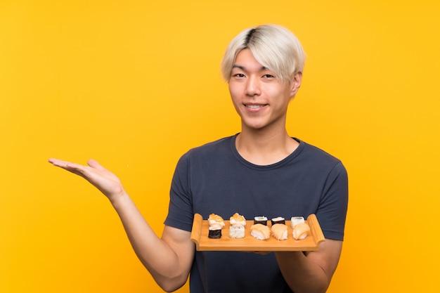 Joven asiática con sushi sobre fondo amarillo aislado con copyspace imaginario en la palma