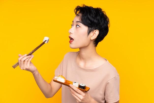 Joven asiática con sushi sobre pared amarilla