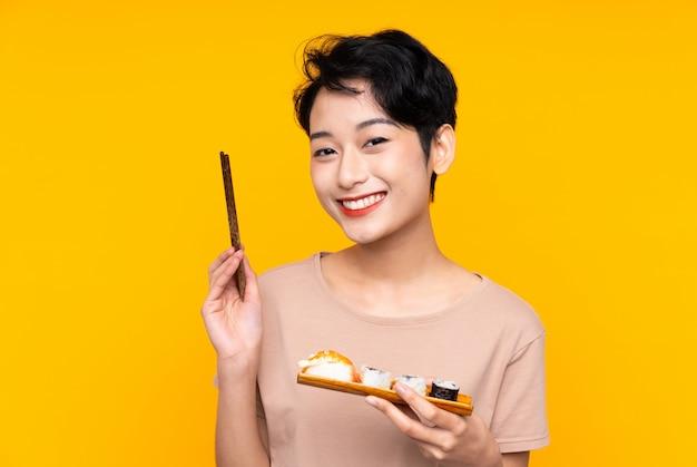 Joven asiática con sushi sonriendo mucho
