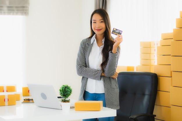 Joven asiática con tarjeta de crédito y caja de cartón