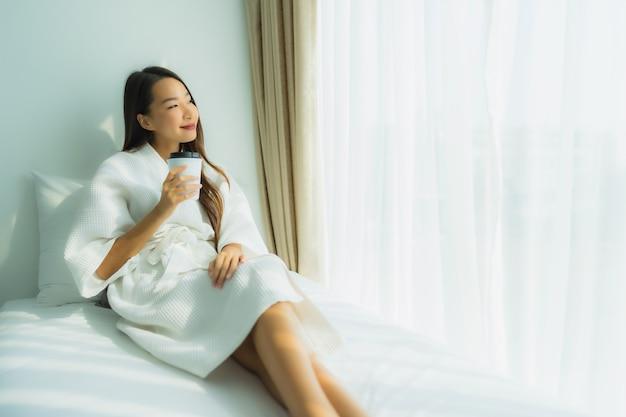 Joven asiática con taza de café en la cama