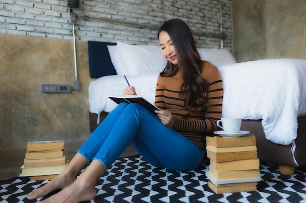 Joven asiática con taza de café y leer libro