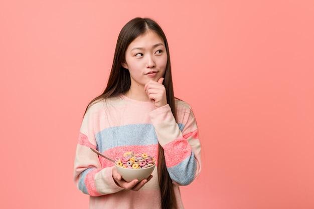 Joven asiática con un tazón de cereal mirando hacia los lados con expresión dudosa y escéptica.