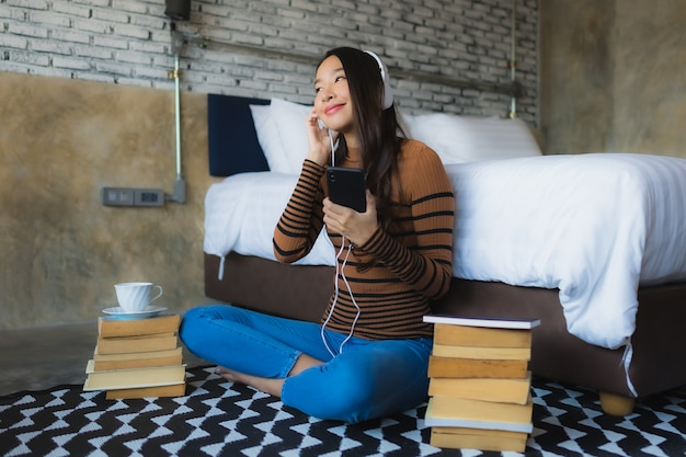 Joven asiática con teléfono móvil inteligente con auriculares para escuchar música alrededor de la taza de café y reservar en el dormitorio