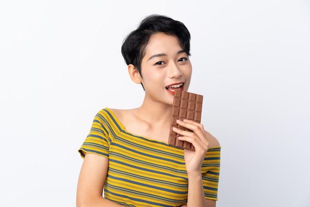 Joven asiática tomando una tableta de chocolate y feliz