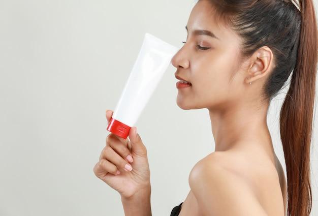 Joven asiática con tubo de crema hidratante