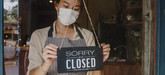 Una joven asiática usa una mascarilla que cambia un letrero de abierto a cerrado en un café con puerta de vidrio después de la cuarentena de cierre por coronavirus.
