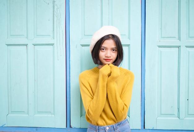 Joven asiática usa suéter amarillo con fondo de puerta azul