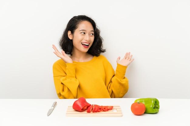 Joven asiática con verduras en una mesa con expresión facial sorpresa