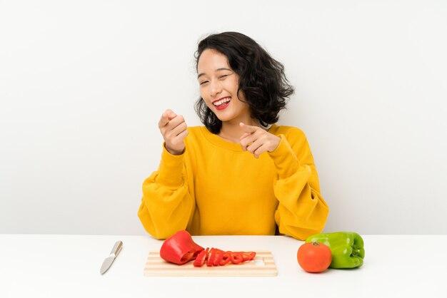 Joven asiática con verduras en una mesa te señala con el dedo