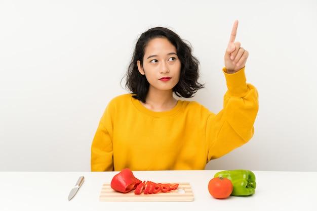 Joven asiática con verduras en una mesa tocando en pantalla transparente