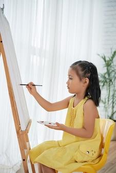 Joven asiática en vestido amarillo sentado frente a caballete en casa y pintura