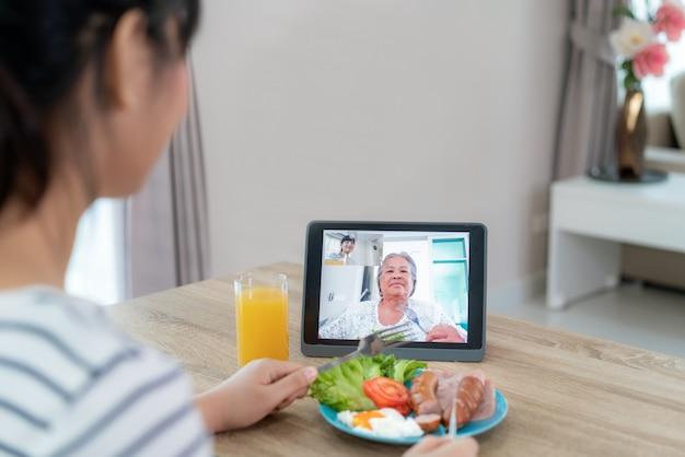 Joven asiática virtual happy hour reuniéndose y comiendo comida en línea junto con su madre