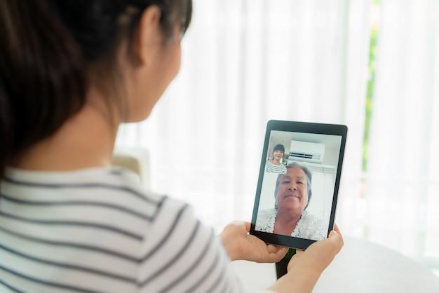 Joven asiática virtual happy hour reunión y hablando en línea junto con su madre en video conferencia con tableta digital para una reunión en línea en video llamada para distanciamiento social.