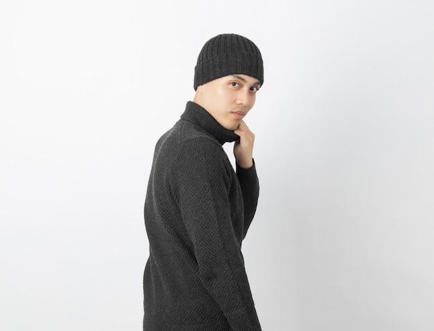 Joven asiática vistiendo suéter gris y gorro mientras mira a la cámara con cara feliz