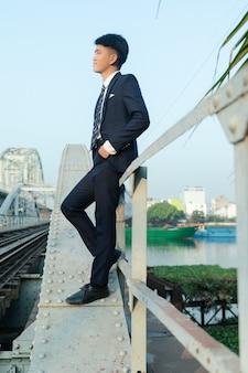 Joven asiático apoyado en un puente mirando lejos