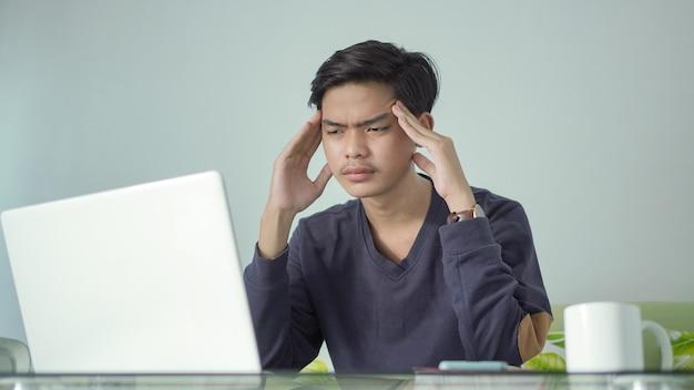 Joven asiático en busca de buenas ideas en su computadora portátil en casa