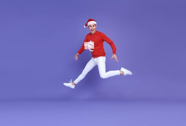 Joven asiático con gorro de papá noel saltando con rojo presenta flotando en el aire.