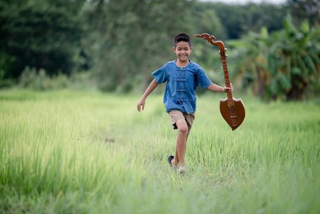 Joven asiático con guitarra hecha a mano en el exterior, país de la vida