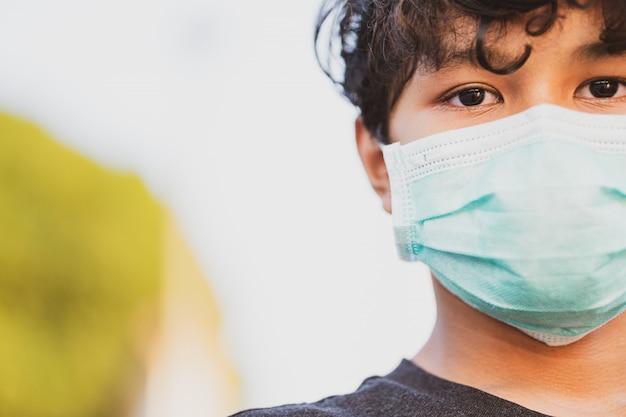 Joven asiático con una máscara protectora, miedo a la gripe y coronavirus