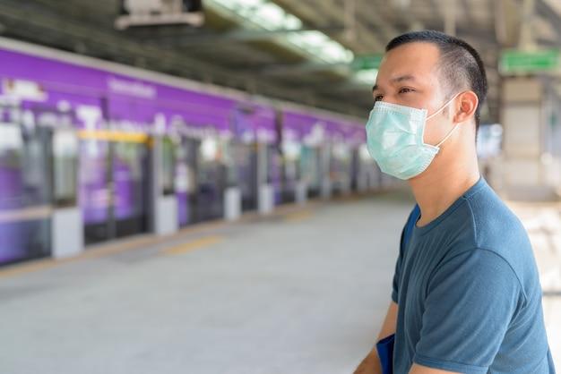 Joven asiático con máscara para protegerse del brote de coronavirus esperando y sentado en la estación de tren del cielo