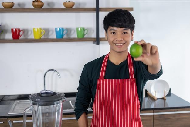 Un joven asiático sonriendo con un delantal rojo mostrando limones verdes borrosa en la mano derecha