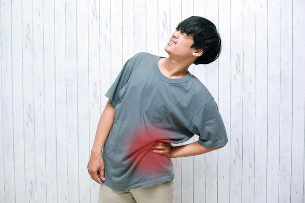 Joven asiático sosteniendo su dolor de espalda en concepto de dolor de espalda o ácido láctico en los músculos y problemas de la columna