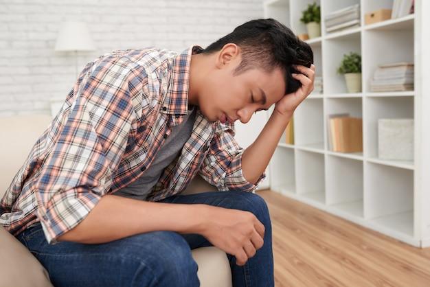 Joven asiático sufferng dolor de cabeza horizontal vista lateral plano
