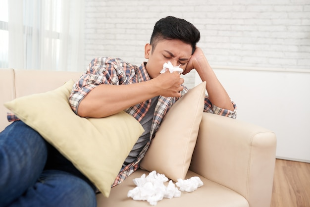 Joven asiático sufriendo goteo nariz tener licencia médica quedarse en casa