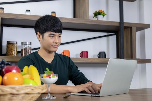 Un joven asiático está trabajando en un negocio en el portátil y mirando el yogur de frutas en el restaurante moderno.