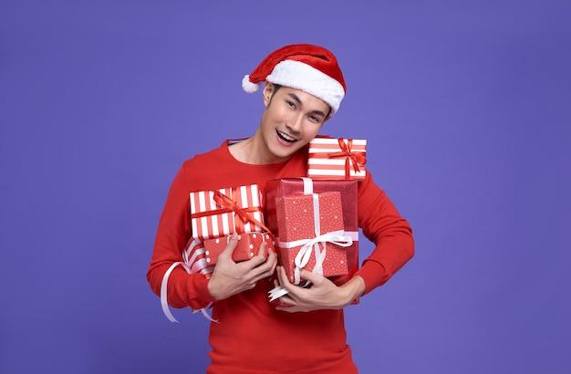 Joven asiático en traje casual rojo con sombrero de santa y sosteniendo una pila de regalos con cara de sonrisa en la pared púrpura. feliz año nuevo concepto.