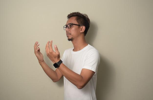 Joven asiático vestido con camiseta blanca orando con levantar ambas manos concepto musulmán