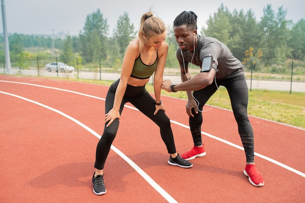 Joven atleta africano que muestra el tiempo a la niña activa mientras ambos están parados en la línea de salida en el estadio al aire libre