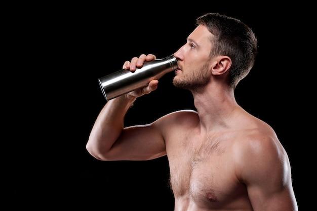 Joven atleta sin camisa de pie y bebiendo agua de una botella de metal después del entrenamiento sobre pared negra