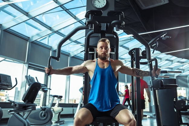 Joven atleta caucásico muscular entrenando en el gimnasio, haciendo ejercicios de fuerza, practicando, trabajando en la parte superior de su cuerpo, tirando de pesas y pesas. fitness, bienestar, concepto de estilo de vida saludable, trabajo.